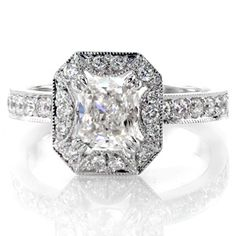 Stunning diamond engagement ring done with micro pave on the band and the halo. The halo has a unique starburst pattern that comes out from under the center stone. Cushion Lotus by Knox Jewelers