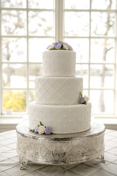 - Bella Rose Photography www.bellarosephoto.com White three layer fondant wedding cake with lavender flower details on silver cake stand.