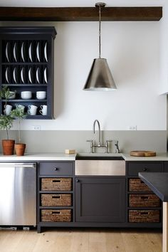 Charcoal gray, stainless steel, blond wood floors, darker brown baskets and pots on the counter, white walls, and white dishes against the dark cabinet.