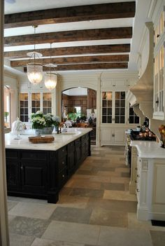 Stunning French Country kitchen with black island, wood celing beams, bell jar pendant lights, and marble counters.
