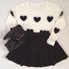 White knit sweater with black hearts. Black skater skirt with black ankle sneakers with printed white poka dots.