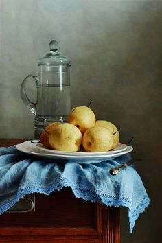 Asian Pears Art Print by Nikolay Panov Classic still life with few yellow Asian Pears on blue folded napkin and tall pitcher with water in old kitchen