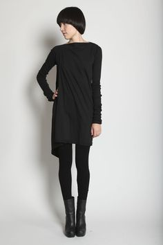 Dry clean. Cotton jersey tunic with draping at right side. Boat neckline. Extralong finely ribbed sleeves. Self-banded asymmetric hemline with unfinished rolled edge at right side. Slips on.