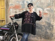 From fabric embroidered by the Rabari of Kutch, this black tunic is the oversized layering piece youll wear time and time again. Its lightweight soft pure wool with flower motifs and mirror embroidery on a black background of bandhani or tie dye dots. Its unlined, and the oversized T shape makes it perfect to wear over a long sleeved thermal T shirt. It has welt pockets too, and all edges are finished with block printed satin bindings. Youll always be cozy, comfortable and feel well dressed…