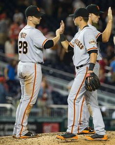 San Francisco Giants' Buster Posey, left, high fives second baseman Joe Panik after a 10-3 win in a baseball game against the Washington Nationals, Friday, Aug. 22, 2014, in Washington. (AP Photo/Evan Vucci)