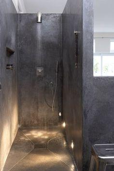 Une salle de bain avec douche italienne en béton ciré