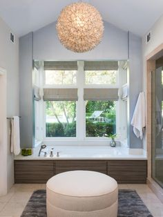Designer Patty Malone used a Caesarstone tub surround, custom laminate tub facing by Terri Robison Design and a custom area rug to create a spa-like bathroom with a blue-gray backdrop.
