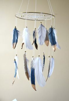 This gorgeous natural feather dreamcatcher mobile will make all your dreams come true :) This mobile can be hung beside a crib, changing table, rocking chair, perfect for a baby boy/ girl nursery, Native American style or tribal bedroom decor. Features made of a sturdy gold metal hoop 10 in diameter. Webbed with white cotton string and a few gold crystal beads on the web. The gold dipped snow white, navy blue, grey and natural color pheasant feathers are attached by gold pony beads. The ...
