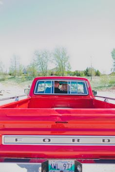 We love this photo of the bride and groom in a pickup truck. Photo by BLF Studios.