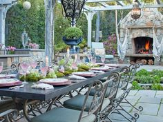 Neutral colors and historic details create this romantic, inviting outdoor dining space. The gray arbor frames the adjacent fireplace, creating a focal point. The arbor also provides much-needed refuge from the California sun.