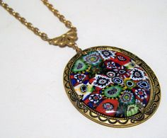 Mid Century Murano Italy millefiori cabochon attached pendant necklace Gorgeous multi color millefiori in an antiqued gold tone setting Pendant is attached to chain Pendant is 2 1/4 x 1 3/8 inches, including bale Necklace is 21 inches long Unsigned piece, very attractive Very good