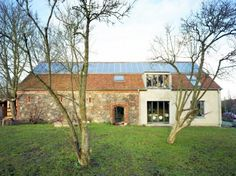 A historic stone barn in Ihlow, Germany has gotten a second lease on life with the addition of a new home and reinforcement of the existing structure.