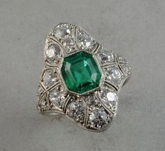 Such a pretty ring that's edwardian in style.  Feel like the setting is so large it distracts from the emerald. Image Source: http://jatelierinc.com/products/edwardian-emerald-ring-in-platinum/