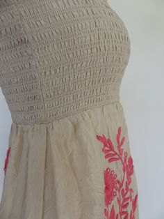 Festival Dress, Juicy Couture Original, designer dresses. One of Juicy Couture's most coveted pieces designed with a hippie inspiration and masterful embroidery. Insanely feminine crushed creamy silk cascades over an underneath skirt slip. Delicate smocked and finely stitched top with stretch for a perfect, stay-put fit. Straight neckline with tasseled self-tie adjustable straps. Exquisite floral and vine embroidery in Pink down skirt, front and back. In Angel/Pink Style