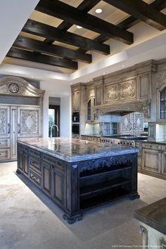 Attention to detail was the key to this luxurious European-style kitchen in Paradise Valley. The cabinets are hand-stained & carved and boast subtle tones and textures and include classical design motifs like the acanthus leaf. The glass paned cabinets feature inset wrought iron and seeded glass. Designed by VM Concept in Scottsdale, AZ.
