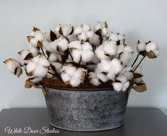 Add some southern charm to your home decor with this rustic cotton boll centerpiece. If you love farmhouse style, this piece is a must have addition to your decor. Perfect for any room of your home. Finished piece measures approximately 16 x 16 x 13 Numerous cotton boll stems are hand arranged inside of a stylish round metal tub. Tub is made of galvanized steel, and has a matte, silver finish. Two rope handles are attached to two opposite sides of the tub. Cotton boll stems feature natural…