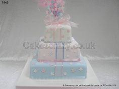 Three tier celebration cake with staggered tiers convered in delicate pink, white and blue. Contrasting stars, hearts and ribbons, and finished with strings of pearls topped with a large wired cake starburst topper
