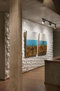 Galeria - Annelise Giordano e Gelise Almeida. O revestimento 3D com formas geométricas confere um ar moderno ao ambiente. O branco contrasta com a madeira do piso e com os detalhes do cimento queimado das vigas. Aliado à iluminação, esse conjunto de texturas ressalta a exposição de obras de arte.