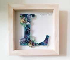 Commission piece: The letter 'L' displayed in blue tones with paper quilled blossom flowers.