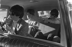 The Beatles with Brian Epstein settle in their car after arriving at RCAF Station Sea Island for their concert at the Vancouver Stadium, Richmond, British Columbia, Canada. (August 22nd, 1964)