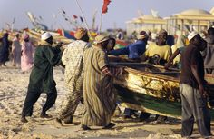 Mauritania, Nouakchott. Fishermen bring a boat up onto the sands of the Plage des Pecheurs (Fishermens Beach) near Nouakchott. The seas offshore from the Mauritanian capital are known as some of the richest fishing grounds in the world.