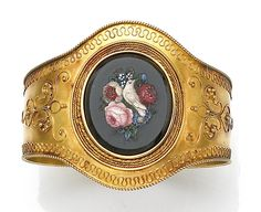 An antique micromosaic bangle bracelet  the hinged bangle centering an onyx plaque depicting a dove and floral motif within a wire twist surround and detail to bracelet, completed by an adjustable keyhole clasp; with Roman hallmark; with fitted box; mounted in eighteen karat gold; diameter: 2¼in.