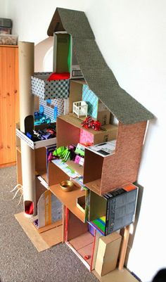 Awesome doll house made out of cardboard boxes, decorated with wrapping paper for wallpaper.