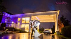 Beautiful photo of the newlyweds in the rain. Love the lights reflecting in the rain drops! Did you know that tradition suggests there's more reasons why rain is GOOD luck on your wedding day than bad? | Lynda Berry Photography