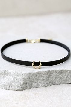 """You'll always stand out in the It-Girl Black and Gold Choker Necklace! A strand of vegan leather with a rhinestone encrusted crescent charm. Necklace measures 12.5"""" long with a 2"""" extender chain."""