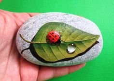 Hand painted rock ladybug on a leaf !  A great handmade painted stone made by me!    Is painted on a smooth sea stone which i have collected from a beach on the Greek island of Ikaria. Is painted with fine art quality acrylic colors and very small brushes for the detail , is signed on the back and covert with strong acrylic stone varnish for protection.    Dimensions approximately :  Height : 9 cm  Width : 5,5 cm    Your art works will arrive carefully packaged.   please for other…