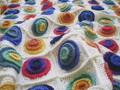 Celebrate colour with this rainbow blanket which features piles of bright circles set against a cream background.