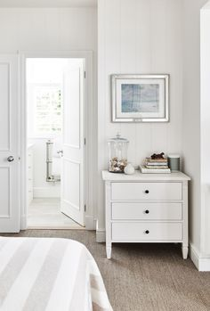 White cottage bedroom features a vertical shiplap clad wall lined with a white French chest adorned with bronze knobs atop a taupe jute rug. Interior Design Bedroom, House Interior, Beige Carpet Bedroom, Home, Beach House Interior, Bedroom Carpet, Cottage Bedroom, White Cottage, Modern Bedroom