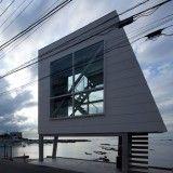 Micro house by Yasutaka Yoshimura slotted between two huge windows