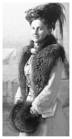 Queen Wilhelmina's dress again lacks the pouter pigeon pouf and she wears a colorful high-necked blouse and fur-trimmed jacket.