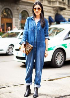 Denim jumpsuit accessorized with black ankle boots and a leopard clutch