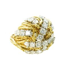 BOUCHERON. A French 18 karat yellow gold, platinum and diamond bombe style ring by Boucheron, Paris. Circa 1965. Signed Boucheron Paris 49125 and hallmarked with AV in a lozenge for A. Vasoort, and French gold and platinum marks. The ring is of textured openwork bombe style, the top set with a total of 34 graduated round brilliant cut diamonds weighing a total of approximately 3.00 carats. The ring has a gross weight of approximately 16.6 grams