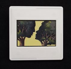This Eric Gill illustration is printed as one of the set of ten Royal Mail postage stamps called 'Greetings Clown' issued in 1995. The unused stamp is titled 'All the Love Poems of Shakespeare'. The decorative image is of a stylised couple in an embrace and encased in a vintage slide mount, with glass, making this a unique piece of jewellery.