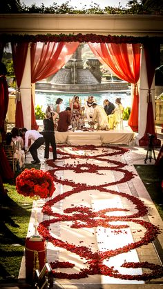 all red roses-red rose petal aisle paired with rose garlands and red drapery for this royal indian wedding.