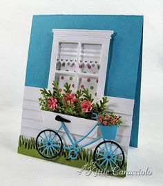 How cute!!!...blue bike with a basket full of flowers in front of a window with a box full of flowers...