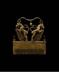 Indian, Hair Comb, 19th—20th century, Gold and red stones. | This heavy, solid-gold hair comb is surmounted by a pair of rearing lions with their tails curling upward. Elaborate foliate forms issue from their mouths. An elegantly curved bar with a central bead connects their heads. The body of the comb features a pair of engraved stylized phoenix birds or dragons with intricate swirling bodies. Two red stones adorn the ends of the comb.