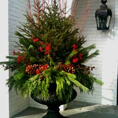 Fresh tree with holiday greens, berries and branches. Great front porch decor for the Holiday Season!