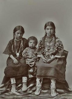 Three children {Beadwork on the leggings and moccasins shows characteristics of one of the Lakota or Dakota Tribes}