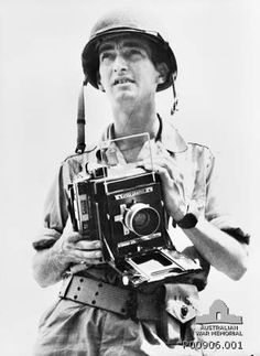 "12-1943. Harold George Dick (Australian) was a  Department of Information Official Photographer during the war. Here is is seen wearing a United States issue ""tin"" helmet and belt, and holding a speed graphic camera, just prior to the landing at Arawe, New Britain. The photographs he took were widely published. He was killed in an air accident in Queensland 12-19-1943, shortly after finishing the Arawe job."