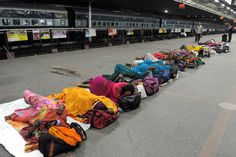 People sleep on a railway platform in Ahmedabad, India late on August 18, 2012. Indian Railways (IR) is an Indian state-owned railway enterprise and one of the world's largest railway networks comprising 115,000 kilometres (71,458 miles) of tracks and 7,500 stations. IR carries over 30 million passengers and 2.8 million tons of freight daily