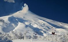 A chairlift with Villarrica Volcano covered in snow in the background