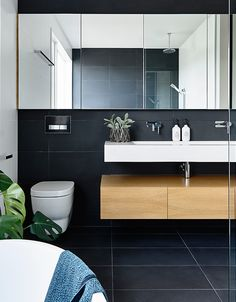 Black tiles on the walls and floor, white vanity and wooden cabinet in this modern bathroom