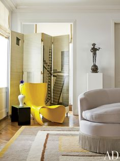 An apartment decorated by Delphine Krakoff includes yellow Mark Newson Felt chair by Cappellini.