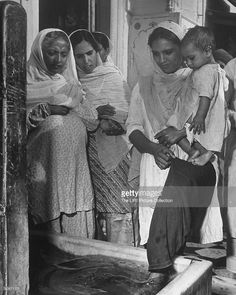 Sikh mother holding child as she washes her feet before entering the Golden Temple for services as other women wait their turn. September 01, 1946. Credit: Margaret Bourke-White.  #Sikh #Kaur