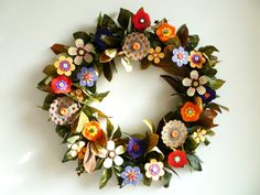 Celebrate Autumn with this warm and earthy wreath. Handmade paper and felt flowers in a fall palette of colors are secured to a wire wreath frame bedecked with green foliage tinged with browns, reds and golds. Six of the flowers sport subtle touches of metallic copper and gold, causing the wreath to glow beautifully when it catches a beam of sunlight. The leaves also have a wonderful warm glow in the light. I am so thrilled that the sun came out this morning long enough for me to capture it…