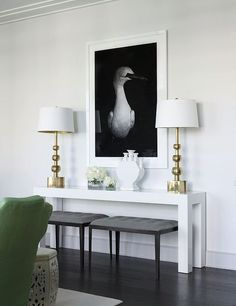 A glossy white Parsons table acts as a console in this stylish living room. Upholstered stools tuck away underneath the table and double as extra seating. - Traditional Home ® / Photo: Werner Straube / Design: Samantha Todhunter